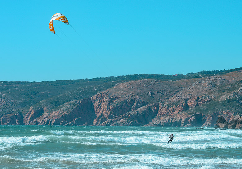 Man kitesurfing on a sunny and clear day at Guincho beach in Sintra, Portugal