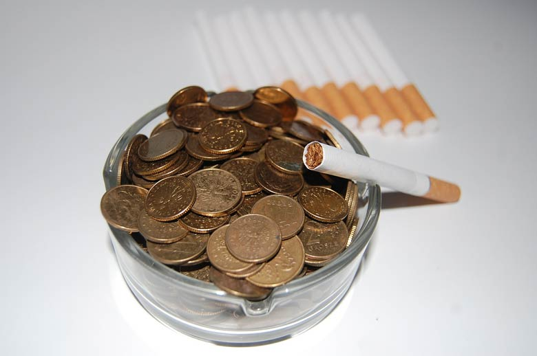 Ashtray filled with coins and a cigarrete