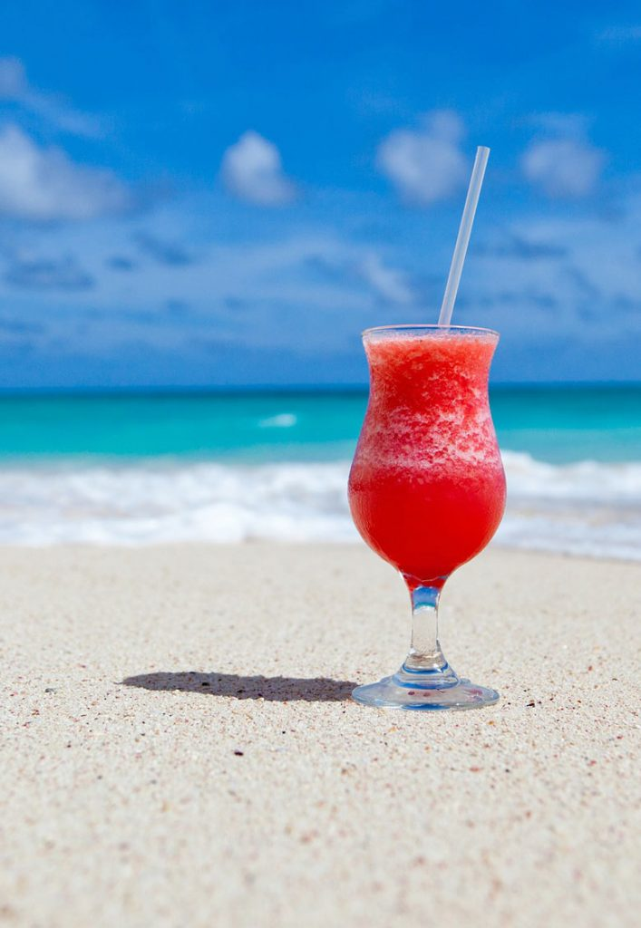 Red drink on the white sand in front of the blue sea