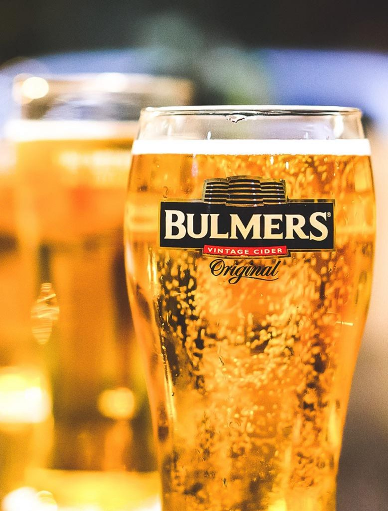 Yellow bubbly drink in a glass of Bulmers cider
