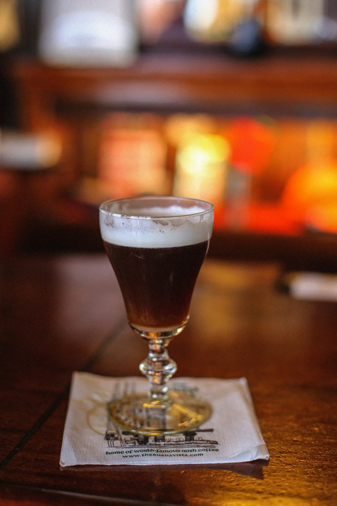 A dark drink with white foam in a glass, is the famous Irish coffee