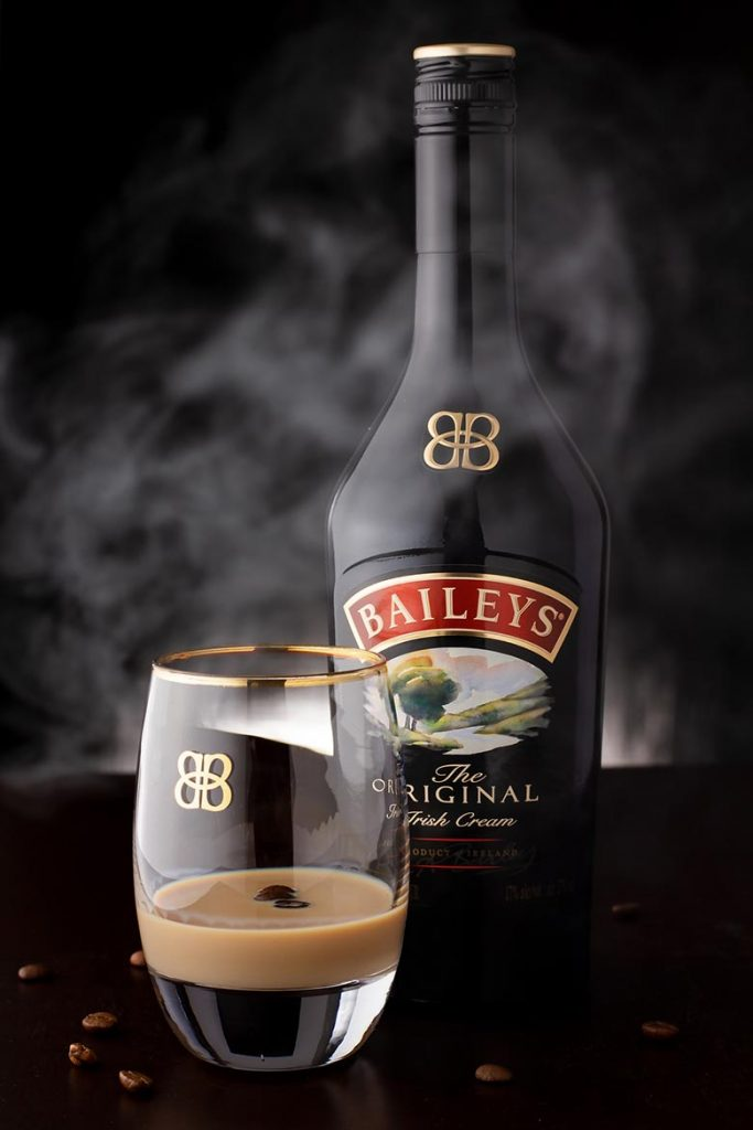 Black bottle of Irish liquor, Baileys, next to a glass with brownish liquid in it. One of the best drinks in Ireland