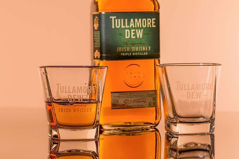 Bottle of the Irish whiskey Tullamore near two glasses, one half filled and the other empty