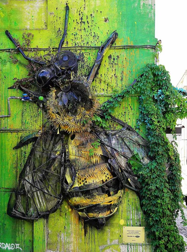 Wall art in Lisbon of a bee on a green wall