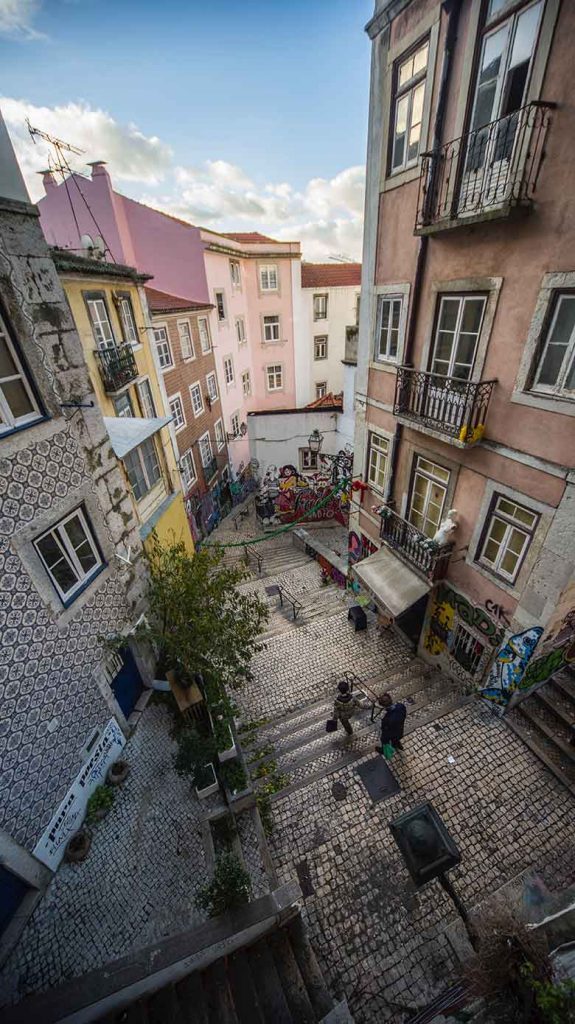 Two people walking downstairs in an alley covered in graffiti in Lisbon