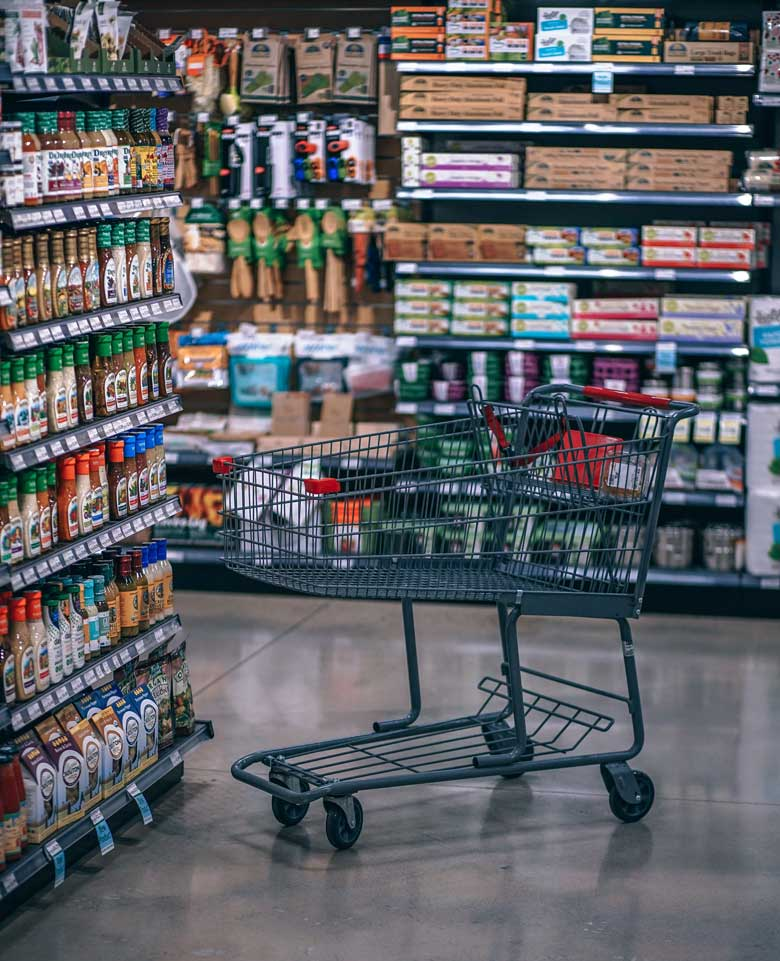 Supermarket cart next to shelves. Tips on how to save money for travel.