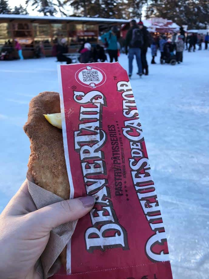 Woman's hand holding a beavertail dough in Ottawa