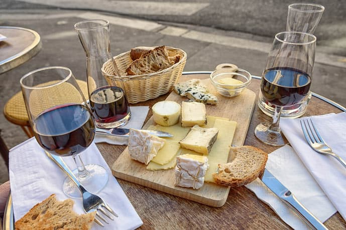 Glass of wine and cheese on a wooden table in Paris