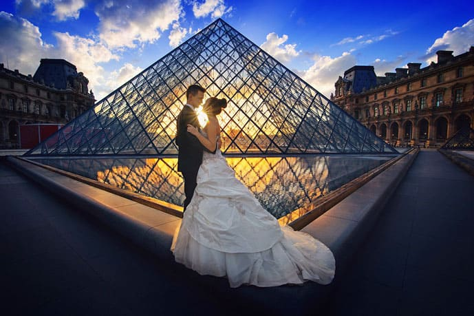 Is Paris the City of Love? A couple standing in front of the Louvre Museum in this romantic city.