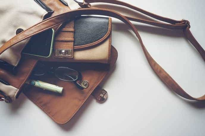 Open travel purse with items rolling out